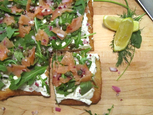Smoked salmon flatbread with arugula, dill, lemon, capers, onions and cream cheese - Super easy and great for parties!